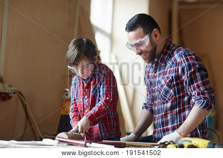 Man and his son in protective eyeglasses woodcarving in workshop