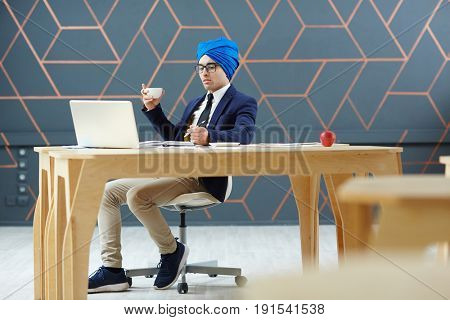 Businessman in turban and formalwear working in office or tv studio