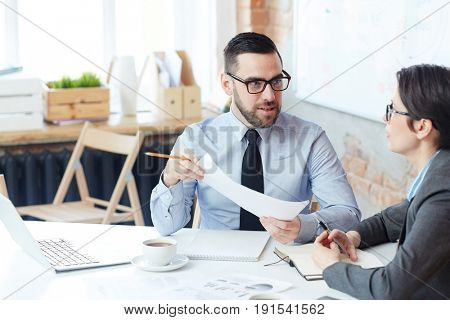 Two analysts brainstorming while discussing ideas for project