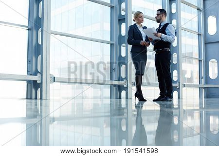 Portrait of contemporary business people, man and woman, discussing work standing in hall of modern office building, copy, space