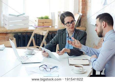 Woman and her boss discussing online data and looking through sales news