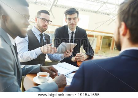 Group of modern businesspeople negotiating partnership agreement during official meeting in sunlight