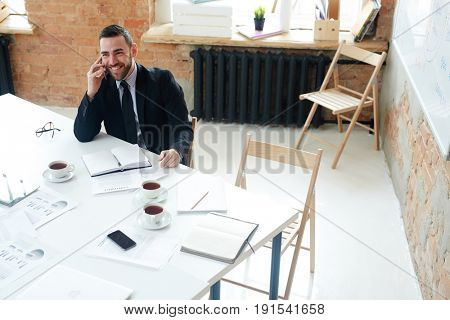 Successful leader consulting employee on telephone