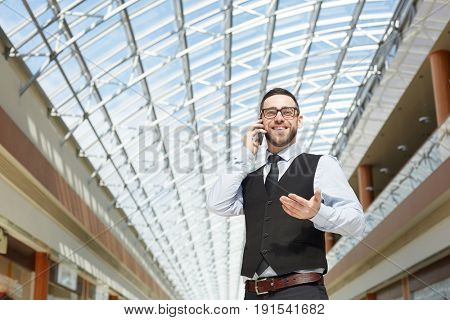 Portrait of modern entrepreneur speaking by phone and smiling in office building under glass roof, copy space