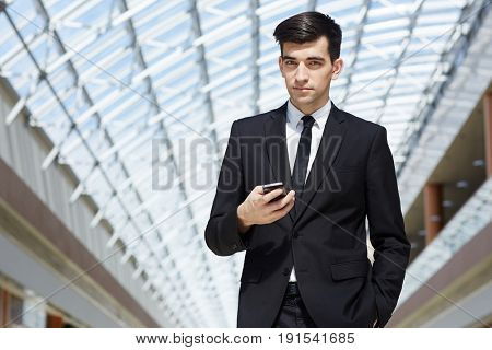 Portrait of confident successful businessman holding smartphone and posing, looking at camera in modern office building under glass roof
