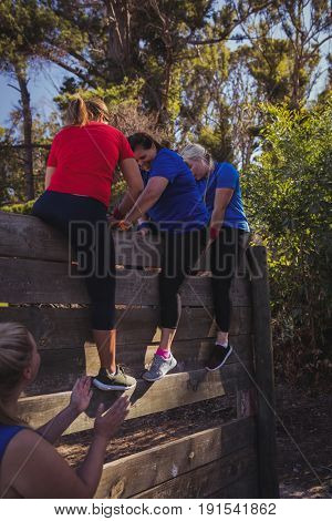 Woman being assisted by her teammates to climb a wooden wall during obstacle course training at boot camp
