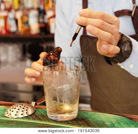 Bartender is dropping bitter into mixing glass
