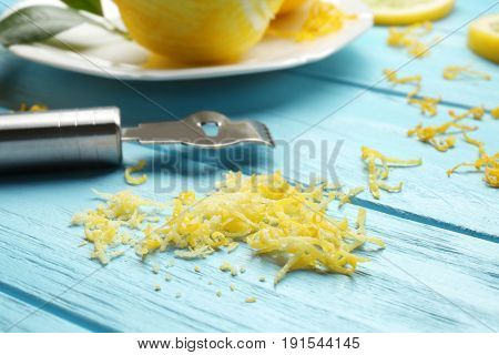 Lemon zest and special tool on wooden table, closeup