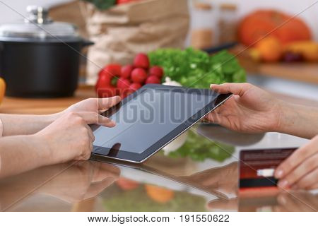 Human hands of two female persons using touchpad in the kitchen. Closeup of two women are making online shopping by tablet computer and credit card. Cooking and shopping concept