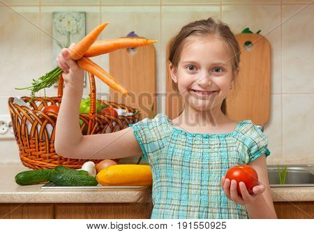 child girl with carrot and tomatoes, vegetables and fresh fruits in kitchen interior, healthy food concept