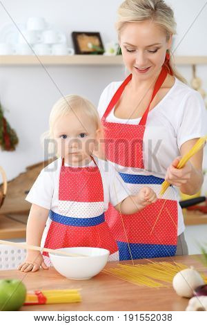Mother and child daughter  cooking pasta or salad for the breakfast. Concept of happy family in the kitchen.