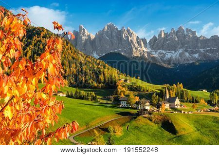 The small village Sankt Magdalena with church and houses in the Villnoesstal with Geisler Dolomites mountains and colorful foliage during autumn in South Tyrol Italy.