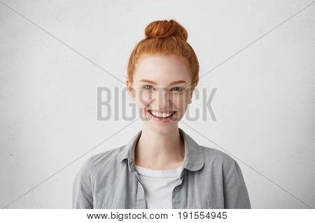 Indoor Portrait Of Stylish Teenag Girl With Freckles And Red Hair Bun Looking At Camera With Cheerfu