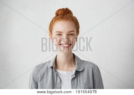 Studio Shot Of Freckled Young Woman With Red Hair Bun Narrowing Her Eyes With Pleasure Smiling Gladl
