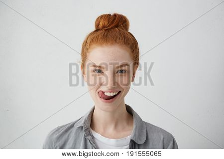 Young Teenage Female With Ginger Hair Knot Sticking Out Her Tongue Having Funny Look Isolated Over W