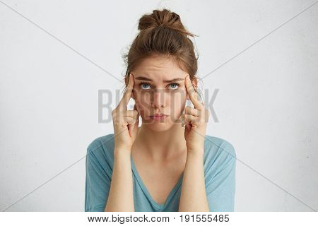 Shot Of Blue-eyed Fair-haired Woman In Casual Clothes Holding Fingers On Temples Trying To Concentra