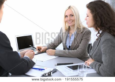 Group of business people at meeting in office. Focus on a beautiful blonde.