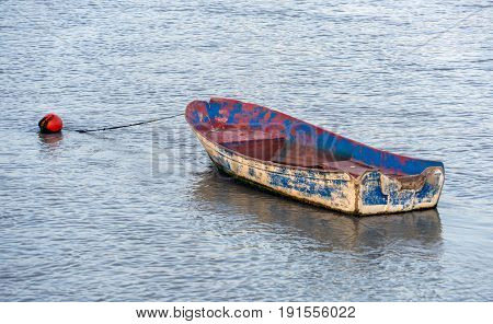A small fishing skiff tied to a mooring bouy in Spain