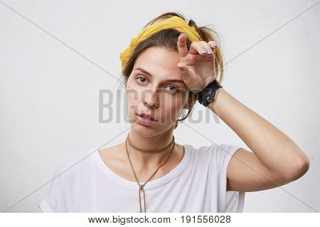 Indoor Shot Of Tired Woman In Casual Clothes Holding Her Hand On Head. Fatigued Housewife Looking Ex