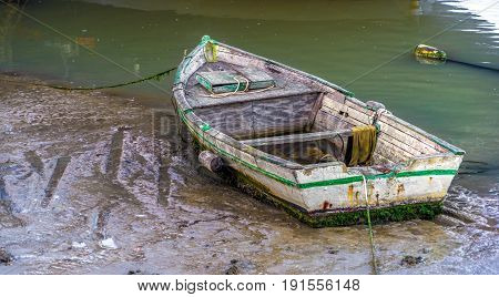 A small fishing skiff sitting in the mud at low tide
