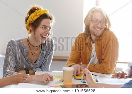 Pleased female in shirt and yellow scarf on head and bearded male with glasses sitting at their working place surrounded with books drinking takeaway coffee having good mood. Emotions and friendship