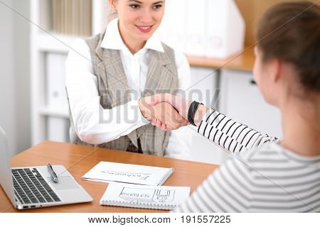 Young business woman shaking hands with a client at the office. Successful insurance business concept