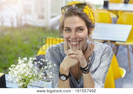 Happy Caucasian Woman Enjoying Vacation While Sitting In Cozy Opened Air Restaurant During Her Summe
