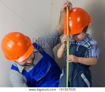 Dad and his little son doing measurement construction tape measure