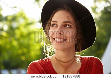 Happy Woman In Red Clothes And Black Hat Looking Aside With Her Steely Look, Tender Smile Waiting Fo
