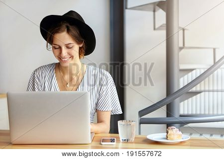 Pretty Young Female Copywriter Wearing Black Hat And Stripped Blouse Working On Laptop Computer, Loo