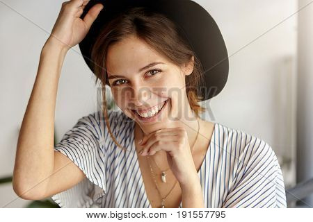 Good-looking Brunette Woman In Black Hat Holding Her Hand Under Chin And On Hat Having Magic Sincere