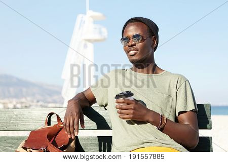 Afro American Male Dressed Casually Sitting At Bench Near Sea Coast Holding Papercup Of Coffee Looki