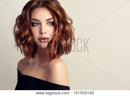 Girl model with sort  red wavy hair. Big curls on the red head . Hairstyle permanent waving