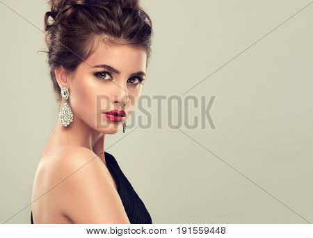 Beautiful model with elegant hairstyle . Beautiful woman with fashion  hairstyle and colourful makeup . Jewelry earrings