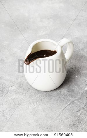 The Melted Chocolate (chocolate Sauce) In A White Sauce-boat On A Light Background