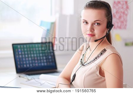 Beautiful business woman working at her desk with headset and laptop .