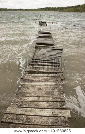 Old wooden walkways. The gray lake. Storm
