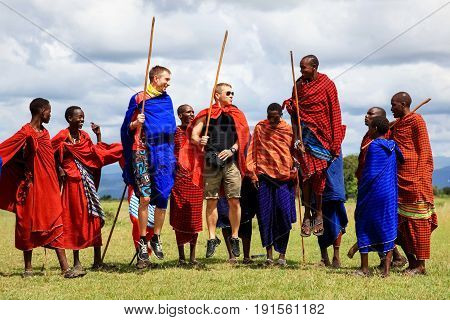 Africa Tanzania Masai Village - March 04 2016: European tourists and locals perform the national dance of the Masai tribe