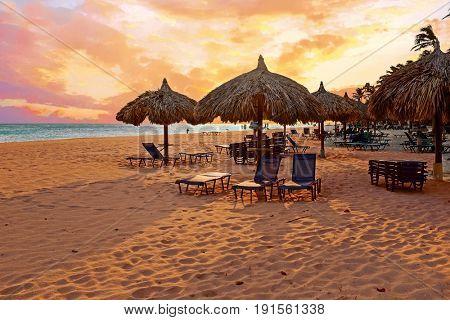 Beach umbrella's on Druif beach at Aruba island in the Caribbean at sunset