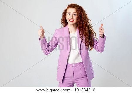 Portrait of successful happy beautiful business woman with red - brown hair and makeup in pink suit with thumbs up. looking at camera with toothy smile studio shot on gray background.