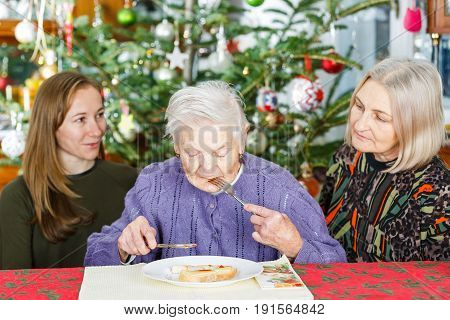 Photo of elderly woman having breakfast with her caregivers