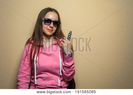 Vape Woman. Portrait Of Young Cute Girl In Pink Hoodie And Sunglasses Holding An Electronic Cigarett