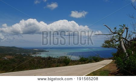 Downward road overlooking Saipan lagoon Road in Marpi looking toward Saipan lagoon with its different shades of blue. Mariana Islands