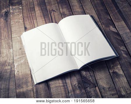 Blank open book brochure or magazine on vintage wooden table background. Mock-up for graphic designers portfolios. Responsive design mockup.