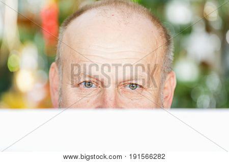 Portrait of handsome elderly man hidden behind white paper