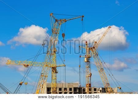 Yellow tower cranes and mobile construction cranes against blue sky background