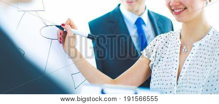 Businesswoman writing on flipchart while giving presentation to colleagues in office .