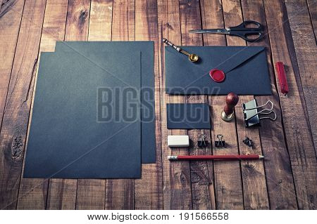 Photo of blank black stationery set on vintage wood background. Mock up for branding identity. ID template.