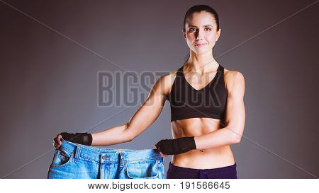 Young fitness woman showing that her old jeans .