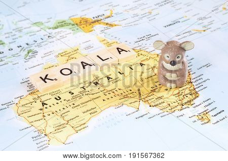 A concept photo with a toy koala and letters on the map.